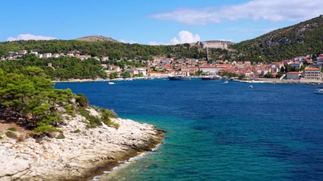 aerial footage with a revealing effect of the hvar old town in croatia - isola video stock e b–roll