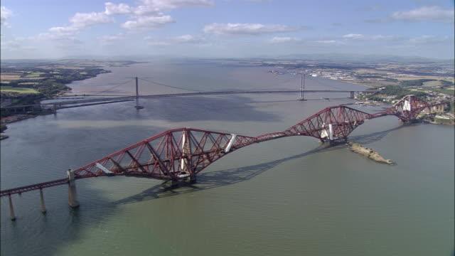 aerial forth bridge and forth road bridge over firth of forth / edinburgh, scotland - fluss firth of forth stock-videos und b-roll-filmmaterial
