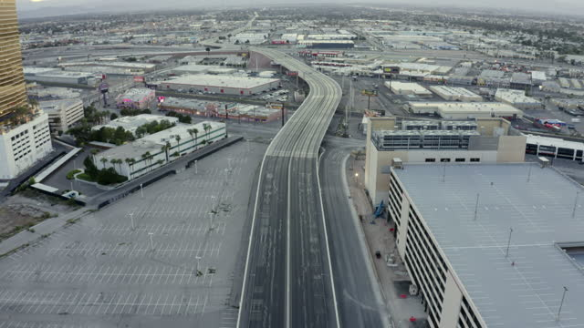 aerial forward: a few scattered cars speed along desolate highway between empty parking lots and garages in downtown las vegas - aerial stock videos & royalty-free footage