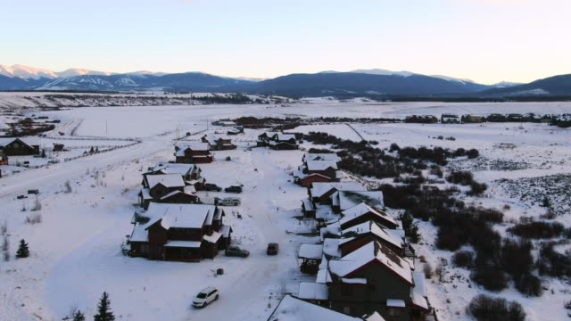 aerial forward: a minivan drives through a snow covered neighborhood in tabernash with view of mountains - lieferwagen stock-videos und b-roll-filmmaterial