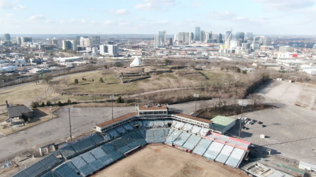 aerial forward: abandoned minor league stadium on outskirts of nashville with skyline of city and plains beyond - remote location video stock e b–roll