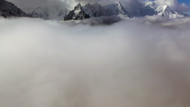aerial forward: amazing sunlit snowy mountains among thick clouds - mount blanc, france - thick stock videos & royalty-free footage