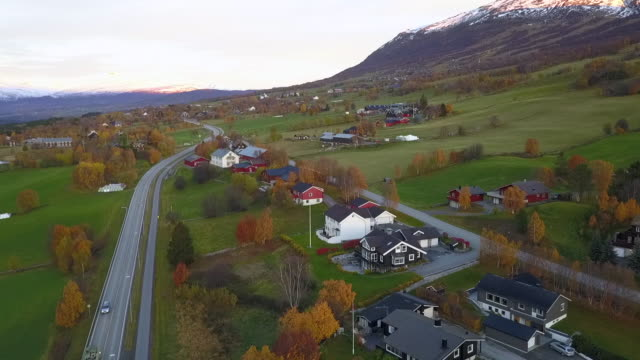 aerial forward: autumn in scenic town among snowy mountains in oppdal, norway - small town stock videos & royalty-free footage