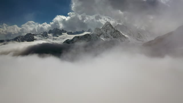 aerial forward: awesome sunlit snowy mountains among thick clouds - mount blanc, france - mont blanc stock videos & royalty-free footage