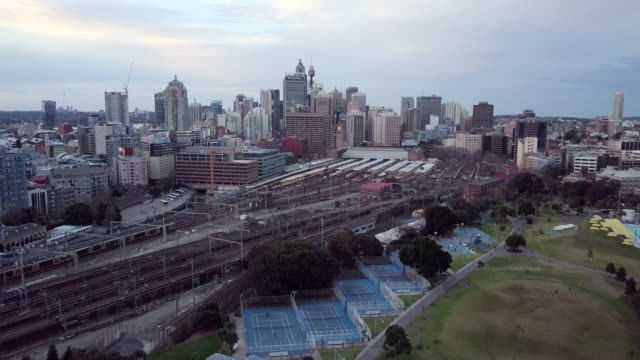 aerial forward: basketball courts, train tracks and city on overcast day, sydney, australia - court stock videos & royalty-free footage
