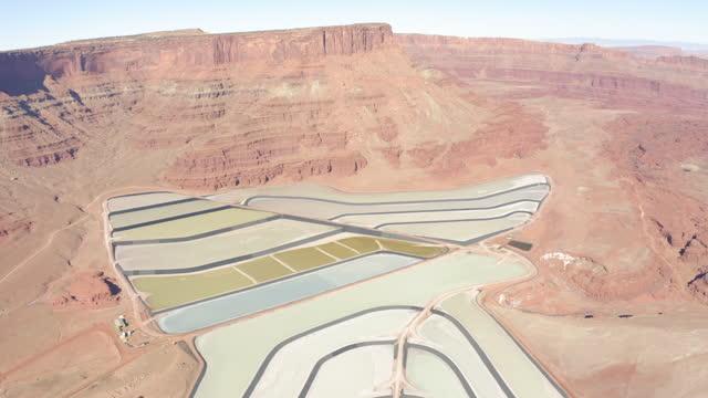 aerial forward: beautiful evaporation ponds against cliffs - moab, utah - 堆積岩点の映像素材/bロール