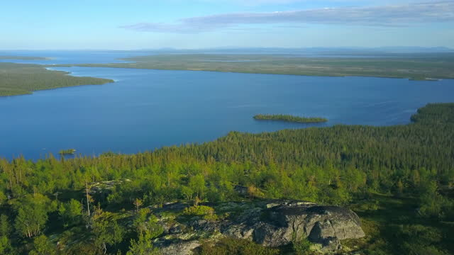 aerial forward: beautiful lake by forest against sky on sunny day - lapland nature reserve, russia - nature reserve stock videos & royalty-free footage