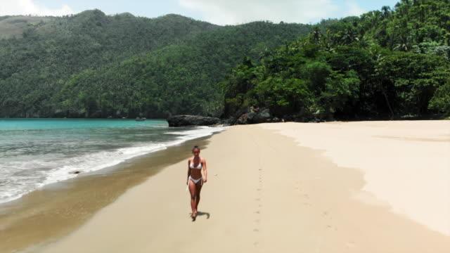 aerial forward: beautiful young woman in bikini walking on exotic beach - ドミニカ共和国点の映像素材/bロール