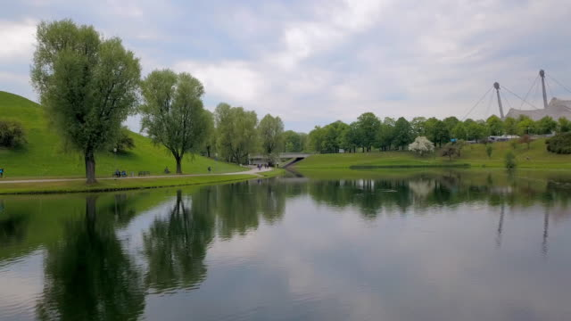 aerial forward: biking in the olympic park beside lake in munich - munich, germany - geschützte naturlandschaft stock-videos und b-roll-filmmaterial