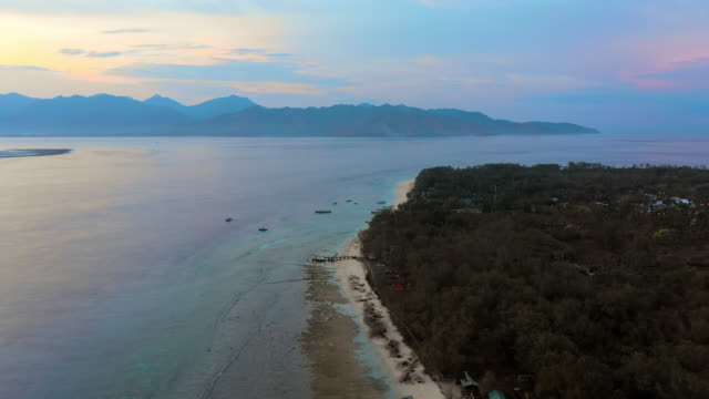 aerial forward: blue tinted mountains in distance, forest covered island on right - gili islands, bali - indonesia beach stock videos & royalty-free footage