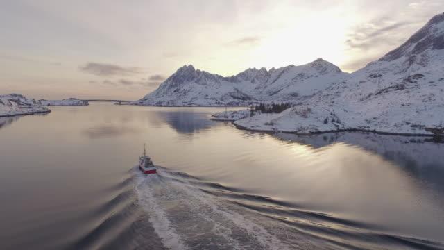 aerial forward: boat slicing through the waters of lofoten norway - lofoten, norway - nordland county stock videos & royalty-free footage