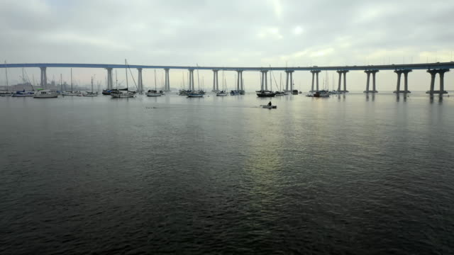 stockvideo's en b-roll-footage met aerial forward: boats floating in water under bridge on cloudy day in san diego, united states of america - san diego
