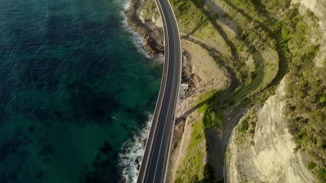 aerial forward: bridge at edge of ocean, bottom of rocky mountain, wollongong, australia - viewpoint stock videos & royalty-free footage