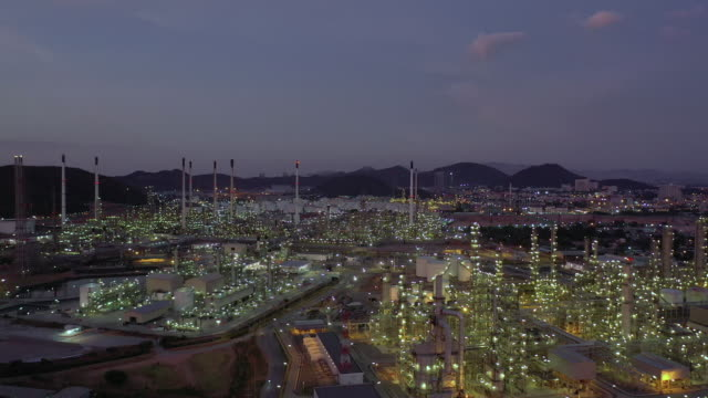 aerial forward: bright light of oil refinery in twilight time - power station stock videos & royalty-free footage