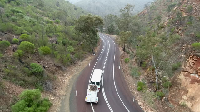 Aerial Forward: Bus Driving On Windy Road Between Tree Covered Mountains - Uluru, Australia