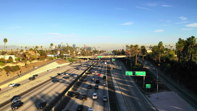 vidéos et rushes de aerial forward: busy highway leading to city in evening in los angeles, united states of america - guide