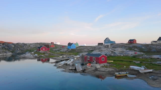 aerial forward: colorful houses by picturesque bay with icebergs in the distance, disko bay, greenland - greenland stock videos & royalty-free footage