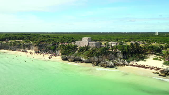 aerial forward: crowded shore with gorgeous green plain behind in tulum, mexico - tulum mexico stock videos & royalty-free footage