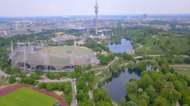 aerial forward descending: trees, water and buildings of olympic park germany - munich, germany - olympische spiele stock-videos und b-roll-filmmaterial
