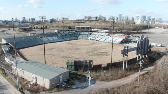 aerial forward: dilapidated abandoned minor league stadium surrounded by empty parking lots as train rolls by - dugout stock videos & royalty-free footage