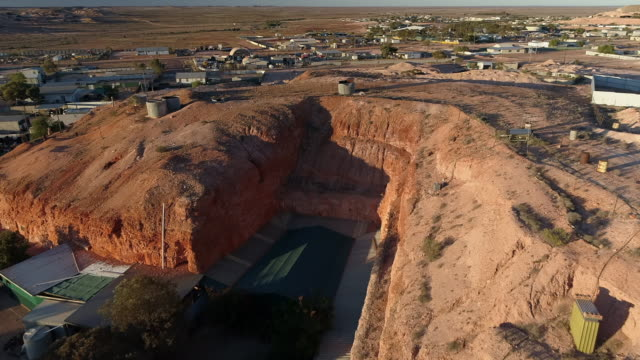 aerial forward: dirt hills next to buildings on large, flat plain - uluru, australia - エアーズロック点の映像素材/bロール