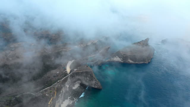aerial forward: fog above rocky island surrounded by bright blue ocean - nusa penida, bali - island stock videos & royalty-free footage