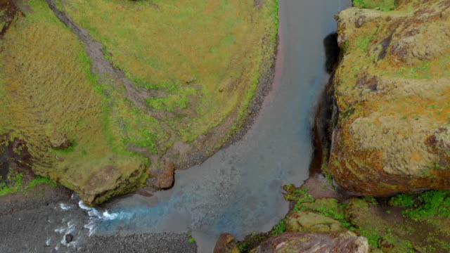 Aerial Forward: Grassy Rocks and Cliffs With River At Bottom in Fjaorargljufur, Iceland