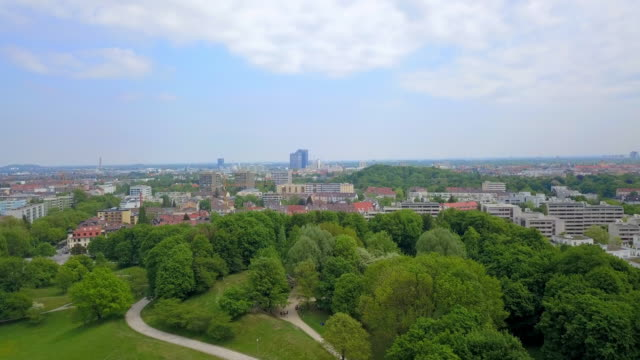 aerial forward: green trees of munich olympic park - munich, germany - schlossgebäude stock-videos und b-roll-filmmaterial