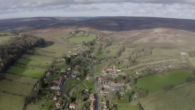 aerial forward: homes covered by the shadow of clouds - north yorkshire, england - village stock videos & royalty-free footage