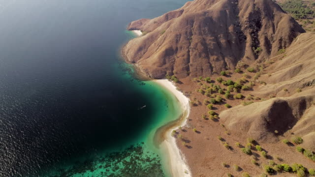 aerial forward: huge mountain of komodo island of indonesia dividing the beach - insel komodo stock-videos und b-roll-filmmaterial