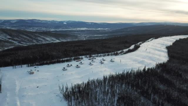 aerial forward: igloos on snowy mountain overlooking valley, fairbanks, alaska - igloo stock videos & royalty-free footage