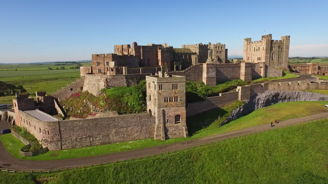 vidéos et rushes de aerial forward: imposing stone castle perched on grassy hill and cliff towers over small village and long grassy plains in the sunshine - bamburgh, united kingdom - british military