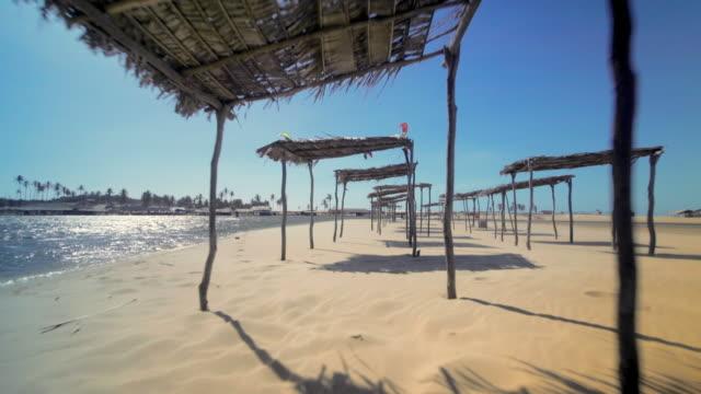 vídeos de stock, filmes e b-roll de aerial forward: kiteboarding on beautiful beach, cumbuco, brazil - américa do sul