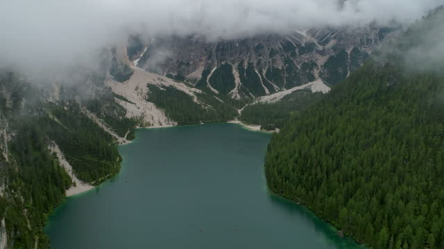 aerial forward majestic view of lake amidst forest, drone flying over clouds - pragser wildsee, italy - oben stock-videos und b-roll-filmmaterial