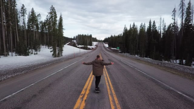 Aerial Forward: Man Skateboarding Freely on the Roads of Montana