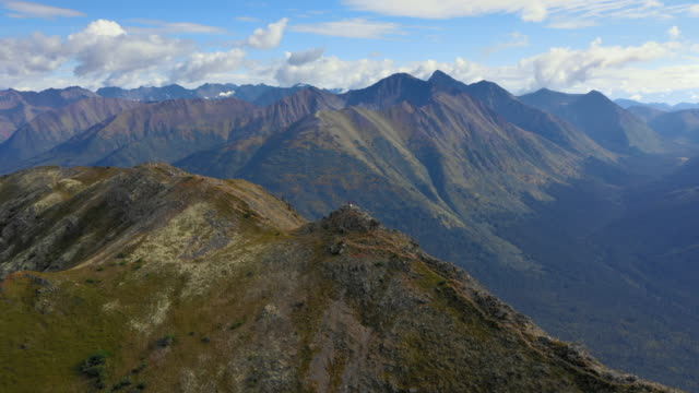 aerial forward: man standing on top of rocky mountain, overlooking valley and mountains - chugach national forest, alaska - chugach national forest stock videos & royalty-free footage