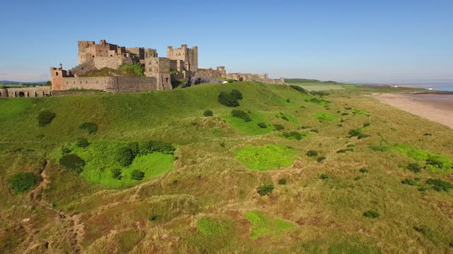 aerial forward: massive stone castle perches on grassy hill high above wide beach on ocean in the sunlight - bamburgh, united kingdom - northumberland video stock e b–roll
