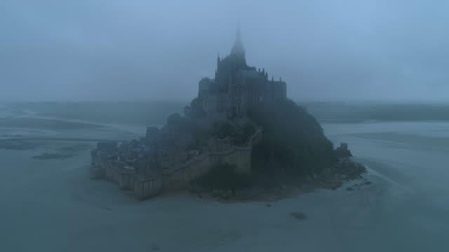 vidéos et rushes de aerial forward: mont saint-michel at dusk in fog with good view of medieval architecture - normandy, france - moyen âge