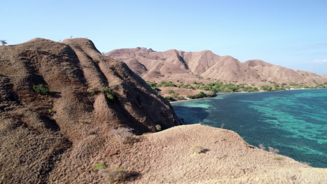 aerial forward: mountains and beach of komodo island in indonesia - insel komodo stock-videos und b-roll-filmmaterial