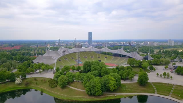 aerial forward pan right to left: big stadium in olympic park munich germany - munich, germany - famous place stock-videos und b-roll-filmmaterial