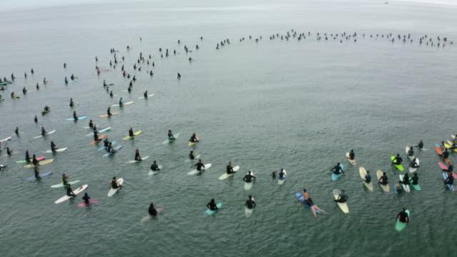 aerial forward pan: surfers splashing water in sea during protest - santa monica, california - aerial stock videos & royalty-free footage