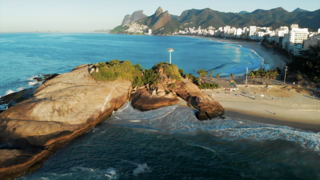 aerial forward: people chilling on scenic beach by modern city - rio de janeiro stock-videos und b-roll-filmmaterial