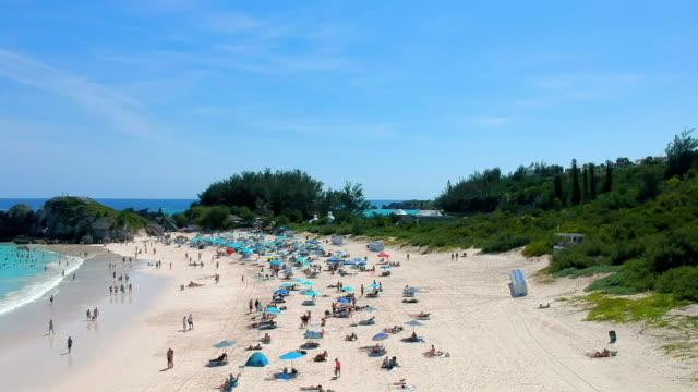 aerial forward: people with umbrellas under the sun of bermuda beach in spanish point, bermuda - bermuda stock videos & royalty-free footage