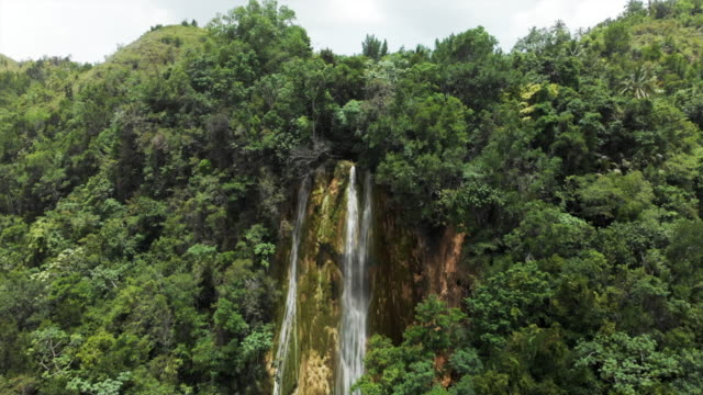 Aerial Forward: Picturesque Waterfall Among Lush Green Jungle