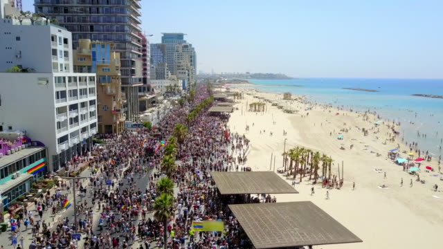 aerial forward: pride parade on scenic promenade along beautiful seashore, tel aviv, israel - promenade stock videos & royalty-free footage