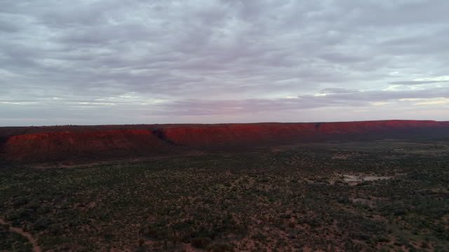 aerial forward: red mountains on large plain with cloudy sky above - uluru, australia - エアーズロック点の映像素材/bロール