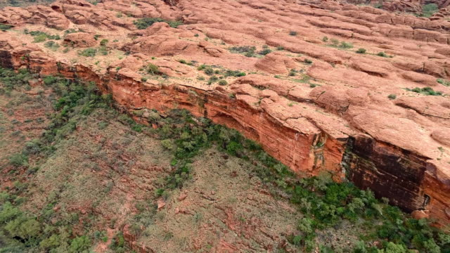 aerial forward: red rocky plain leading to cliff - uluru, australia - geology stock videos & royalty-free footage