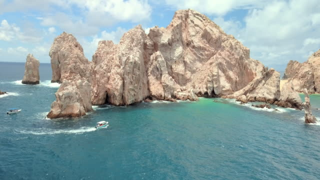 aerial forward rise: rock formation cliffs and sea - cabo san lucas stock videos and b-roll footage