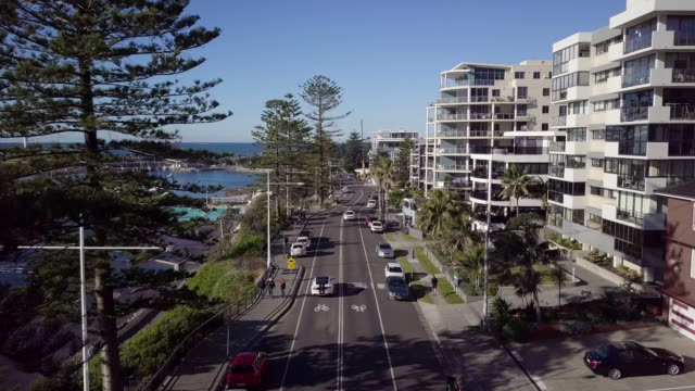 aerial forward: road, city and boats on shore of blue ocean, wollongong, australia - stationary stock videos & royalty-free footage
