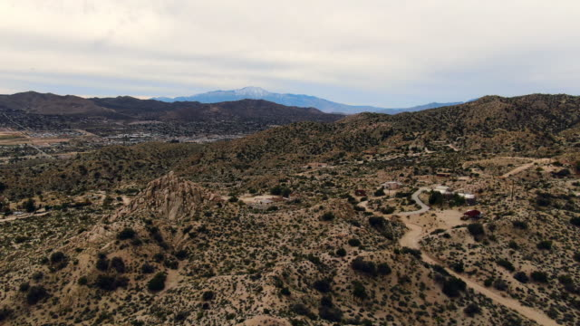 aerial forward: rocky hills in mojave desert with scrubby brush and a distant view of the snowy rocky mountains - deserto mojave video stock e b–roll